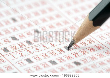 Close up of a lottery ticket and pencil isolated on white background.