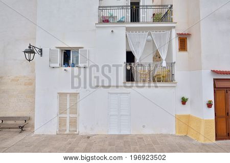 Nice adriatic house facades with shutters and different light colours. Monopoli south Italy