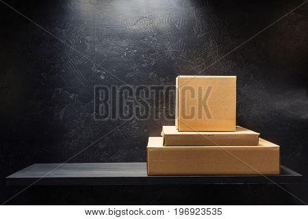 cardboard box on wooden shelf at black background surface