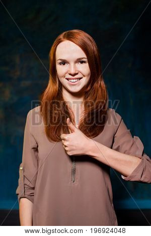 beautiful young red-haired teen showing thumb up and smiling