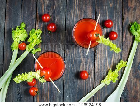 Tomato juice in glass with celery cherry tomato on wood background closeup. Top view