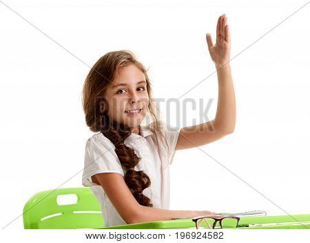 Excited happy schoolgirl with raised hand wanting to answer