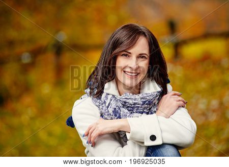 Beautiful happy woman sitting on tree trunk in forest
