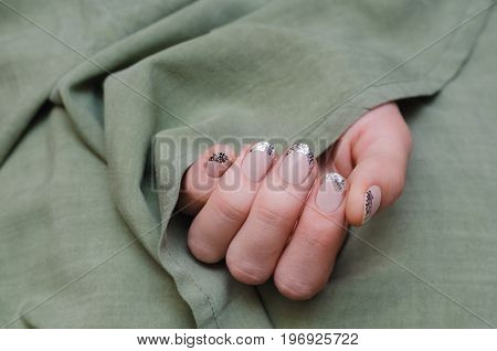 Beautiful female hand with glitter french manicure on green background.
