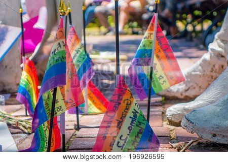 ORLANDO, USA - MAY 05, 2017: Small gay flags in the ground, place where Omar Mateen, killed 49 people and wounded 53 others in a terrorist attack hate crime in a gay nightclub in Orlando, Florida, United States.