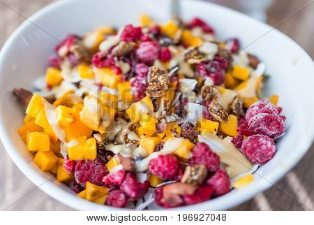 Chopped Persimmon, Raspberries, And Figs In Bowl With Tahini Macro Closeup