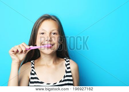 Portrait of beautiful girl with toothbrush on blue background