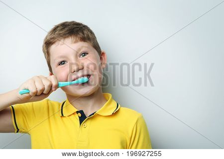 Portrait Of Young Boy With Toothbrush On Grey Background
