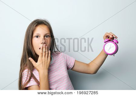 Portrait of beautiful girl with alarm clock on grey background