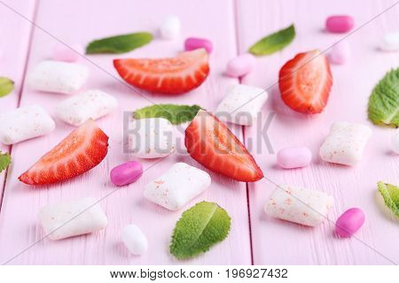 Chewing Gums With Mint Leafs And Strawberries On Wooden Table