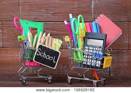Shopping Carts With School Supplies On Wooden Table