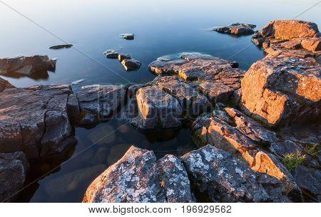 Rocks Of Stony Coast In Calm Water Of Lake