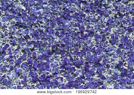 Part of the wall covered with small pieces of purple glass or quartz. Pieces of glass fixed with cement or concrete on the wall. The slides are located in a chaotic manner.