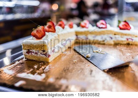 Slices Of A Layered Vanilla Cake With Cream Topped With Strawberries