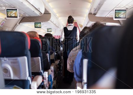 Interior of commercial airplane with passengers on seats during flight. Stewardess in dark blue uniform walking the aisle. Horizontal composition.