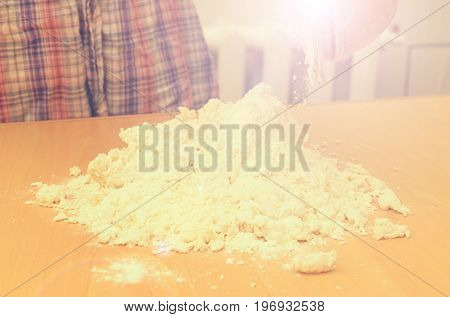 A woman kneads a homemade dough for pizza production