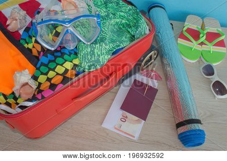 Travel and vacations concept. Open traveler's bag with clothing accessories tickets and passport. Suitcase with different things prepared for travel