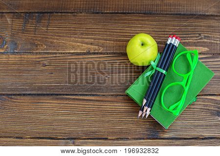 Pencils and glasses a book and a delicious apple on a wooden background. Top view. The concept is back to school.