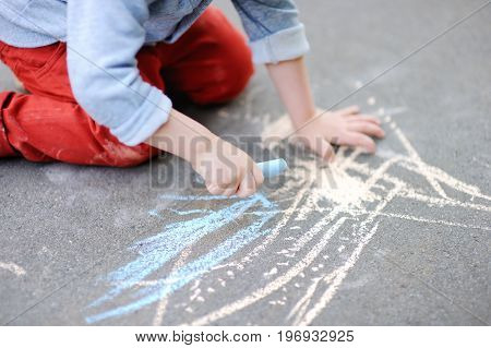 Closeup Photo Of Little Kid Boy Drawing With Colored Chalk On Asphalt.