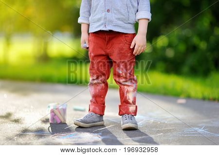 Close-up Photo Of Little Kid Boy Drawing With Colored Chalk On Asphalt.