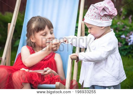 Older sister takes care of her younger sister when playing together outdoors in the garden symbolize care for children