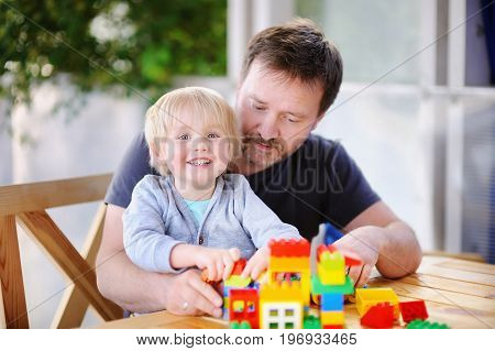 Little Boy With His Father Playing With Colorful Plastic Blocks At Home