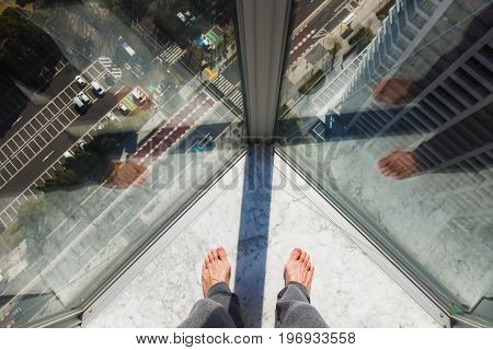 Man's foot against the window. A barefooted man stands by the window. Top shooting .