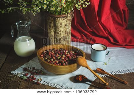 Rustic still-life with strawberries, milk and a bouquet of chamomiles