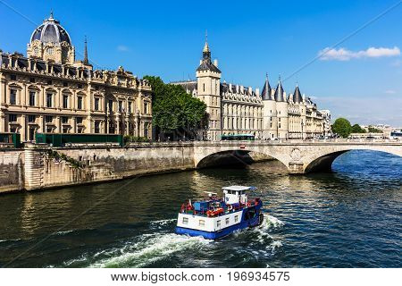 View of the Seine River with cruise tour boat and Conciergerie Castle. Castle Conciergerie is a former prison located on west of the Cite Island and today it is a part of Palais de Justice. Paris France