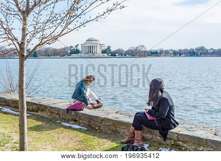 Washington Dc, Usa - March 17, 2017: Young Girls Sitting On Edge Looking Over Tidal Basin And Thomas
