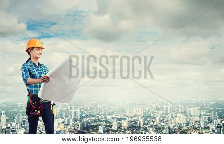 Engineer woman with blueprint on modern city landscape