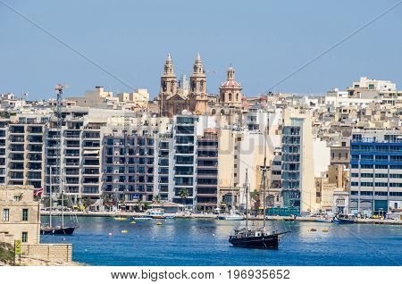 Sliema Malta - June 4 2017: Sliema Waterfront densely covered with modern buildings Sacro Cuor Parish Church and sailing boats as seen from Valletta.