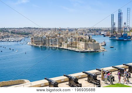 Senglea Malta - June 4 2017: Senglea peninsula as seen from the Upper Barrakka Gardens with its waterfront the St.Philip's Chapel dome bastions of Fort Saint Michael and Saluting Battery with the guard showing a cannon to the tourists