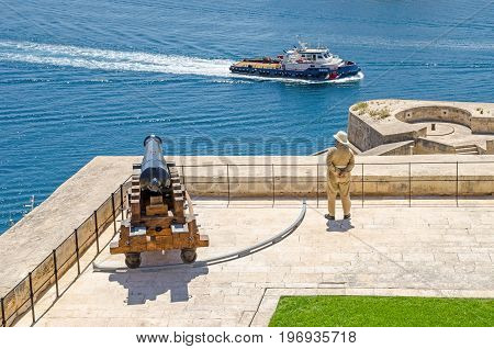 Valletta Malta - June 4 2017: View of Saluting Battery from the Upper Barrakka Gardens with the guard in uniform and a cannon and a passing ship in the Grand Harbour