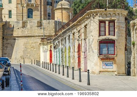 Valletta Malta - June 4 2017: A typical narrow street with the old limestone buildings with colorfull doors and city walls of St.Barbara Bastion in a background near Liesse.