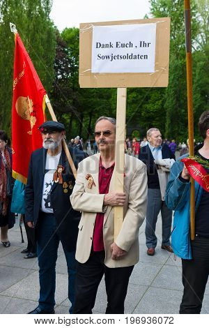 BERLIN - MAY 08 2015: Victory in Europe Day. Treptower Park. Communist activists at the memorable event. Text in German: Thank you Soviet soldiers.