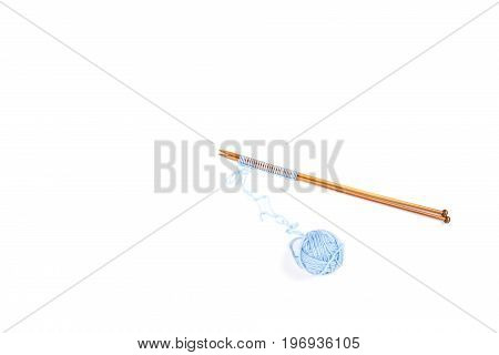 Wooden knitting needles and blue yarn ball on white background