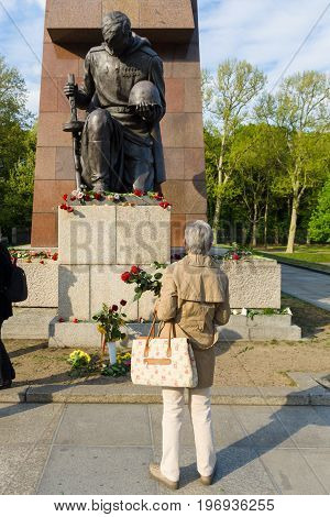 BERLIN - MAY 08 2015: Victory in Europe Day. Treptower Park. A woman lays flowers at the statue of a kneeling soldier.