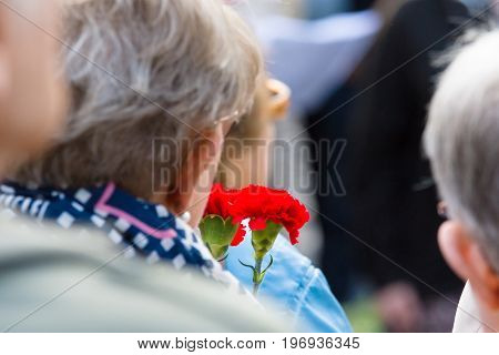 BERLIN - MAY 08 2015: Victory in Europe Day. Treptower Park. Participants of commemorative events with bouquets of carnations.