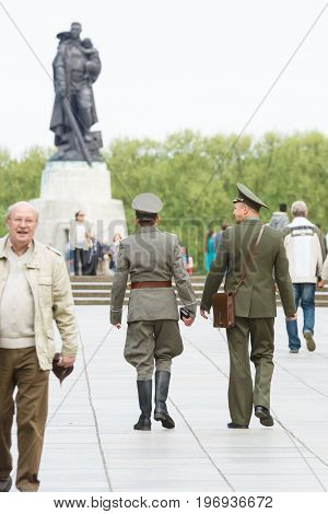 BERLIN - MAY 08 2015: Victory in Europe Day. Two military officers in the form of the Soviet Union and the German Democratic Republic going on the background of the sculpture of a soldier in Treptow Park.