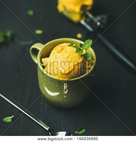 Refreshing summer dessert. Mango sorbet ice cream scoops with fresh mint leaves in green cup over black wooden background, square crop. Clean eating, healthy, weight loss, alkaline diet food concept