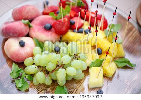 Festive food. Canape with fruits. bunch of grapes, juicy peaches, fresh mint, sweet pineapple, bright strawberry. The taste of summer and fresh fruit