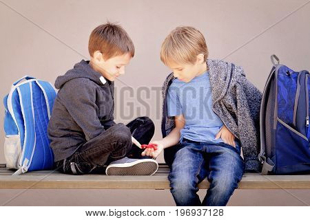 Primary education, school, friendship concept - two boys with backpacks sitting, talking and playing with spinner after school