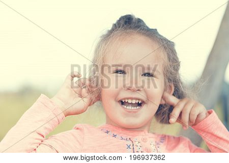 Sweet cute little girl outdoors with opened mouth outdoors portrait