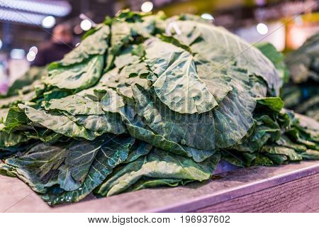 Closeup Of Pile Of Collard Greens In Market Store