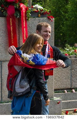 BERLIN - MAY 09, 2015: Enamoured with the Russian flag and symbols are photographed against the backdrop of a memorial to Soviet soldiers.