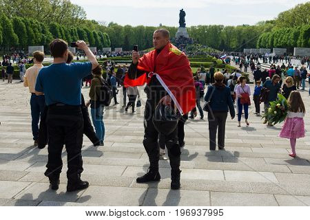 BERLIN - MAY 09, 2015: BERLIN - MAY 09 2015: Victory Day in Treptower Park. The man with the flag of the Soviet Union is photographed against the backdrop of Soviet War Memorial.