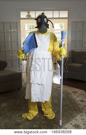 Mature Woman In Haz Mat Suit With Broom And Dust Pan