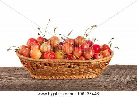 Yellow cherry in a wicker basket on a wooden table with a white background.