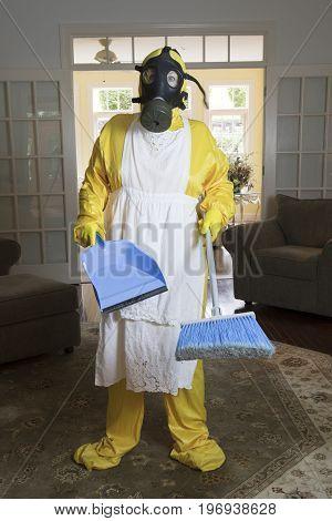 Mature Woman In Haz Mat Suit In Living Room With Broom
